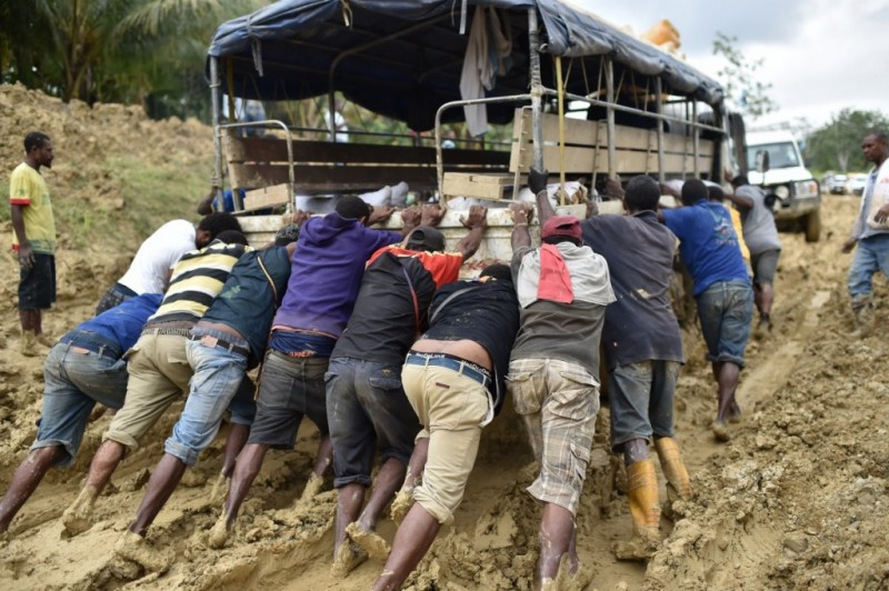 People try to dislodge a truck stuck in the mud in Papa New Guinea